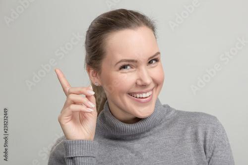 Fotografía  Hübsche Frau im grauen Rollkragenpulli freut sich über eine Idee