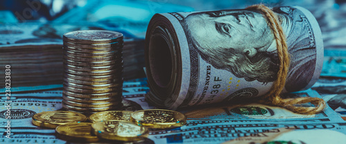 Fotografía  A roll of dollars with coins on the background of scattered one hundred dollar bills in blue light