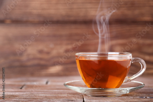 Poster Thee Cup of tea with steam on brown wooden table