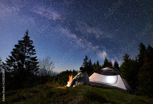Fototapeta Man tourist sitting alone near illuminated tent at burning campfire on grassy valley, enjoying night blue starry sky with Milky way, pine trees forest on background. Beauty of nature, tourism concept obraz na płótnie