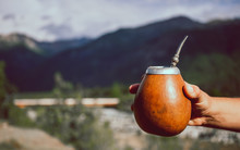 Man Holding Calabash Yerba Mate In Nature. Travel And Adventure Concept. Latin American Drink Yerba Mate