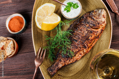 Fototapeta  Grilled dorado fish with lemon and greens on plate on wooden background