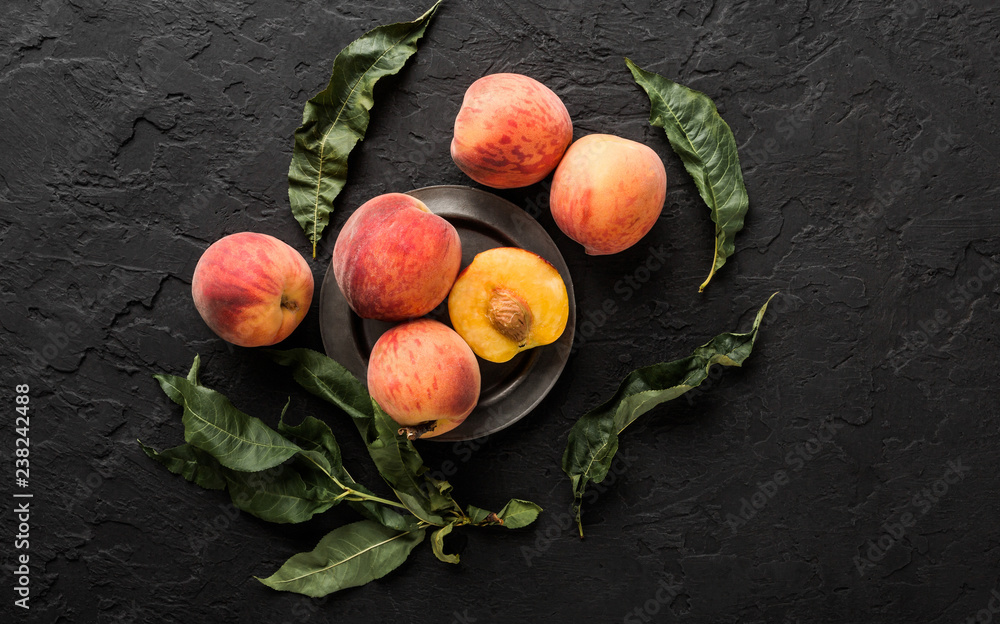 Fototapeta Ripe peaches on black stone background. Healthy food concept, top view, copy space