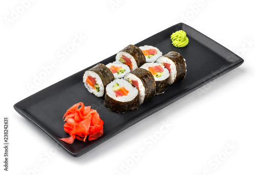 Sushi Roll - Maki Sushi with cucumber, avocado, salmon and cream cheese on black plate isolated over white background. Japanese cuisine