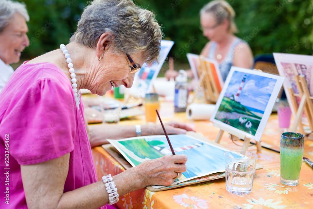 Fototapety, obrazy: Senior woman smiling while drawing with the group.