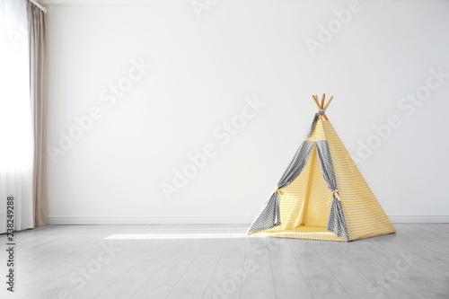 Cozy play tent for kids as element of nursery interior in empty room with space for text