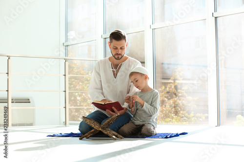 Muslim man and his son reading Koran together indoors