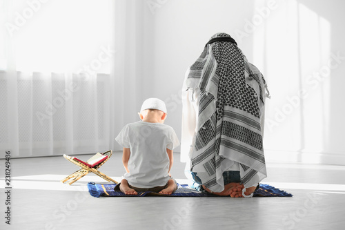 Muslim man and his son praying together indoors