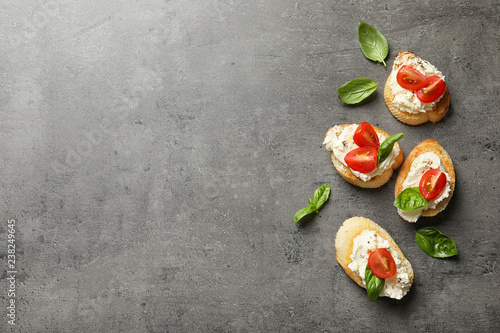 Pieces of baguette with tasty cream cheese and tomatoes on gray table, flat lay. Space for text