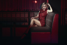 Beautiful Long-legged Blond Model With Provocative Make Up Wearing Red Short Fitted Sequin Dress Relaxing On The Square Sofa In Night Club. Text Space
