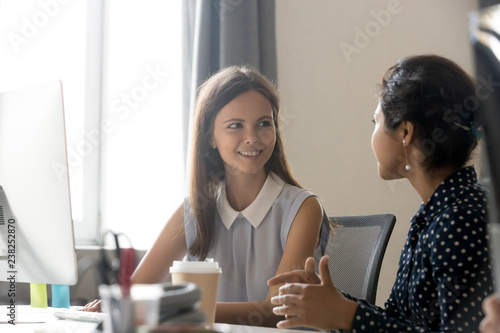 Photo Young smiling female employee listen carefully, talking with female colleague at