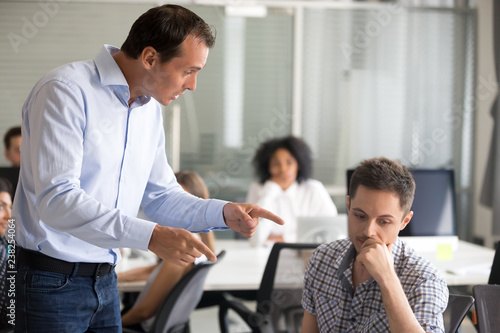 Fotografía Angry boss scolding frustrated incompetent employee at workplace, dissatisfied l