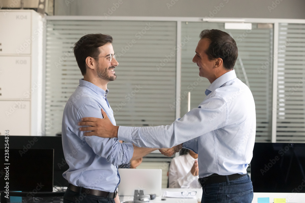 Fototapeta Friendly middle aged boss handshaking male successful employee, congratulate confident worker with promotion, business achievement, thank for good work results, expressing respect, rewarding
