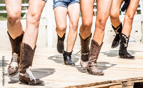Stampa su Tela  Cowgirl girls legs in boots dancing