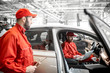 Two male auto mechanics in red uniform diagnosing car with computer at the car service