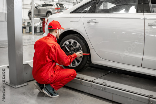 Handsome auto mechanic in red uniform fixing disk for wheel alignment at the car Wallpaper Mural