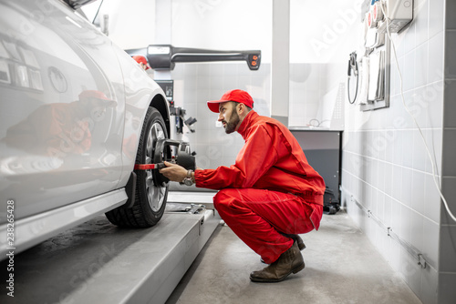 Fototapeta Handsome auto mechanic in red uniform fixing disk for wheel alignment at the car service obraz