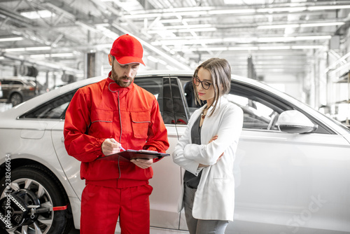 Fototapeta Young woman client with auto mechanic in red uniform standing with some documents at the car service obraz