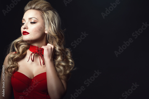 Beautiful blond model with perfect make up and scrapped back hair wearing red corset strapped top trying to take off tied up choker to take a breath Wallpaper Mural