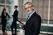 handsome senior businessman looking at his smartphone and in to the camera