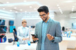 Young mixed race man dressed smart casual and with eyeglasses trying out smart phone. Tech store interior.