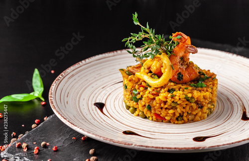 The concept of Spanish cuisine. Paella with seafood, shrimps, squid and greens. Beautiful serving in the restaurant.