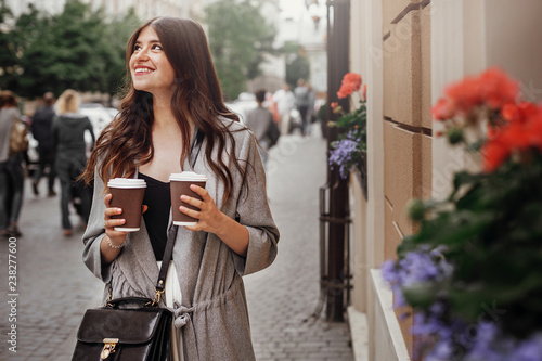 Gorgeous Young Woman With Two Cups Of Coffee Smiling And Walking In