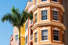 Condos, Condominiums Colorful, Orange Yellow Painted Building Corner Facade Exterior With Windows, Palm Tree, Real Estate Property In Florida Or Spain