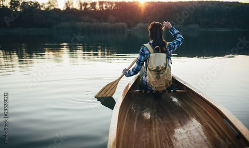 Travel girl paddling the canoe on the sunset lake
