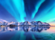 Northern Lights And Snow Covered Mountains In Lofoten Islands, Norway. Aurora Borealis. Starry Sky With Polar Lights And Snowy Rocks Reflected In Water. Night Winter Landscape With Aurora, Sea. Travel