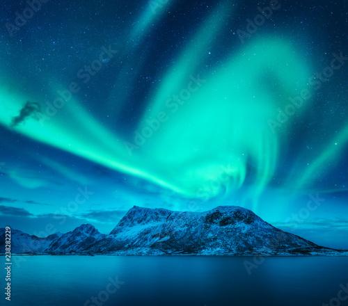 Keuken foto achterwand Noorderlicht Aurora borealis above the snow covered mountain in Lofoten islands, Norway. Northern lights in winter. Night landscape with green polar lights, snowy rocks, blue sea. Beautiful starry sky with aurora