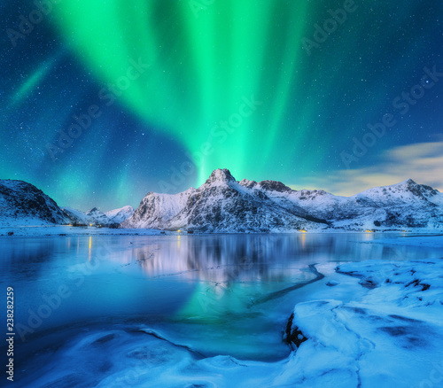 Aurore polaire Aurora borealis over snowy mountains, frozen sea coast and reflection in water in Lofoten islands, Norway. Northern lights. Winter landscape with polar lights, ice in water. Starry sky with aurora