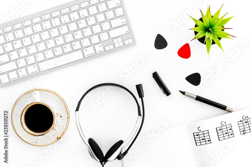 Fototapeta Headphone with paper note, keyboard and coffee in music studio for dj or musician work white background top view obraz na płótnie
