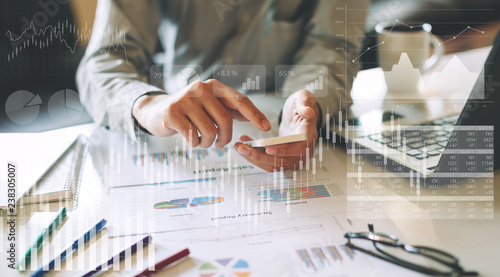Fototapeta businessman investment consultant analyzing company financial report balance sheet statement working with digital graphs. Concept picture for stock market, cash, fund,and business economy flow. obraz