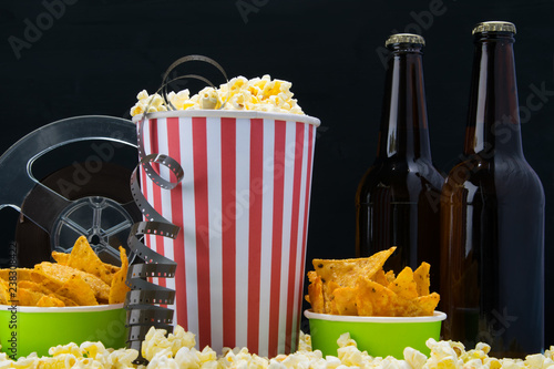 set of beer snacks while watching a movie, background popcorn and nachos