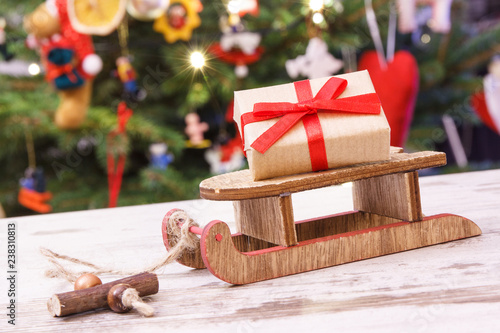 Wrapped Gift On Wooden Sled For Christmas And Christmas Tree With