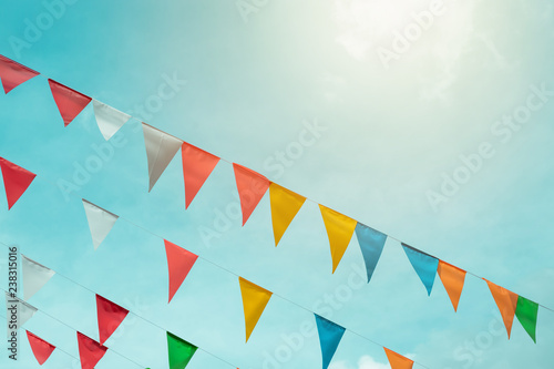 Fotografie, Tablou Fair flag bunting colorful background hanging on blue sky for fun fiesta party e