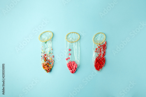 Fotografía Condoms filled with multicolored confetti and confectionary dressing on a pink b