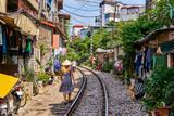 Fototapeta Uliczki - Hanoi city railway Perspective view running along narrow street with houses in Vietnam