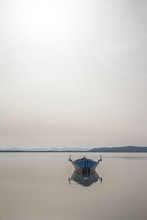Fishing Boat Anchored In A Sea Bay With Flat Water That Merges With The White Sky