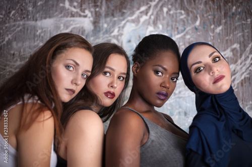 Obraz na plátně  Portrait of four girls with different skin color and nationality in the studio