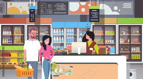 Fotografía  retail woman cashier at checkout supermarket couple customers holding basket wit
