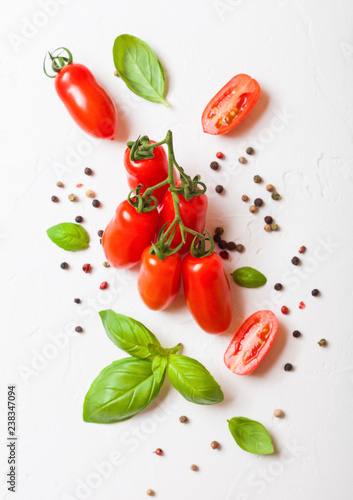 Organic Mini San Marzano Tomatoes on the Vine with basil and pepper on white kitchen background