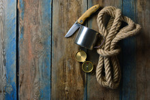 Hunting Saver Wallpaper. Brutal And Sever Background With A Copy Space. Rope, Knife, Compass And Cup On A Weathered Wooden Table.