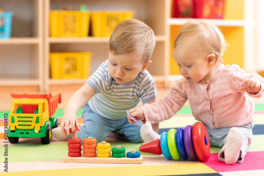 Fototapety, obrazy: Preschool boy and girl playing on floor with educational toys. Children toddlers at home or daycare.