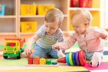 Preschool Boy And Girl Playing On Floor With Educational Toys. Children Toddlers At Home Or Daycare.