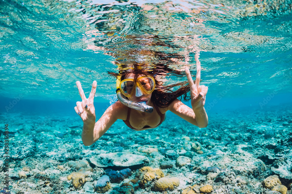 Fototapeta Happy young woman swimming underwater in the tropical ocean - obraz na płótnie