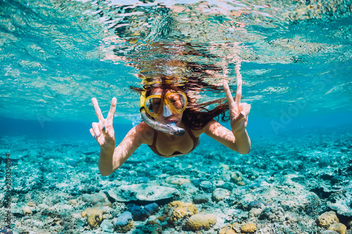 Fototapeta Happy young woman swimming underwater in the tropical ocean obraz na płótnie