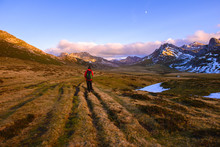 Anonymous Traveler Walking In Valley Towards Beautiful Mountains