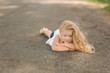 Little girl lie on the road near big alley